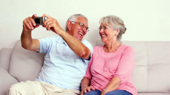 Happy senior couple taking a selfie on the couch - stock footage