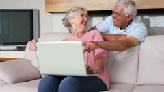 Senior couple using laptop together - stock footage