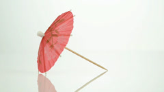 Pink paper cocktail umbrella in rotation Stock Footage
