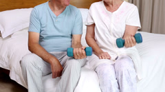 Senior couple sitting on bed lifting dumbbells Stock Footage