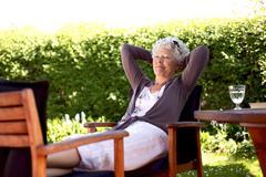 Elder woman resting in backyard garden Stock Photos