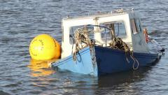Submerged blue fishing boat partly under water Stock Footage