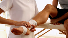 Man getting his ankle wrapped by the physiotherapist - stock footage