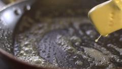 oil falls on a hot pan stock footage cooking food - stock footage