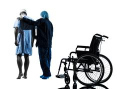 injured man walking away from  wheelchair with nurse silhouette - stock photo