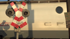 Freight train on cross at railway crossing, red flashing lights signal, railroad Stock Footage