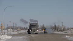 flatbed transport truck turning, cold winter, through frame, long shot - stock footage