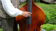 Folk artist in national clothes fingers play with contrabass Stock Footage