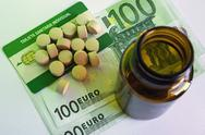 Stock Photo of tablets and pill bottle, concept of pharmaceutical copayment
