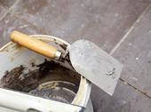 Stock Photo of dirty trowel and bucket on building site. renovation at home