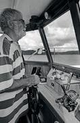 old sailor navigating his boat - stock photo