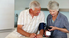Senior woman taking her husbands blood pressure Stock Footage