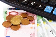 calculator, coins and a hundred euro bill - stock photo