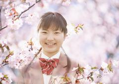 Smiling junior high school girl and cherry blossoms - stock illustration