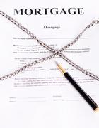 mortgage. contract entwined chain and pen - stock photo