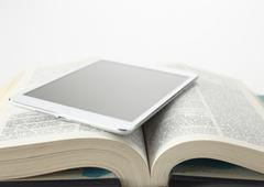 Encyclopedia and a tablet PC - stock photo
