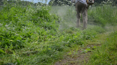 Gardener man cut grass with weed cutter and water drops fall Stock Footage