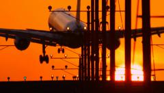Airplane jet plane landing in airport at sunset, flying into sun. Slow motion. Stock Footage