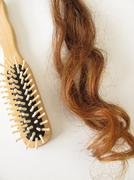 Genuine auburn hair strand and a hairbrush - stock photo