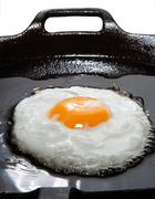 wonderfull frying egg with oil in a black cast-iron pan - stock photo