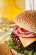 Classic cheeseburger with beer on background Stock Photos
