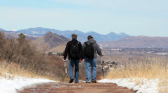 Two men hiking on a path with mountains in background Stock Footage