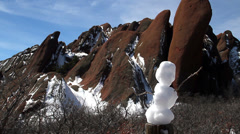 Mini snowman with cool huge red rocks in background Stock Footage