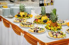 richly served banquet dessert table with fruits and cakes - stock photo