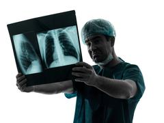 doctor surgeon radiologist examining lung torso  x-ray image silhouette - stock photo