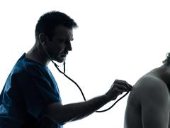 doctor man listening with stethoscope hearbeat silhouette portrait - stock photo