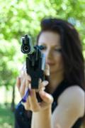 Woman aiming pneumatic gun - stock photo