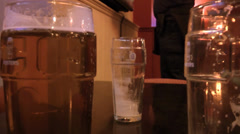 Three glasses on beer, full and empty in a pub HD - stock footage