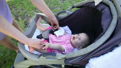 Mother tending to her baby girl in her pram in the park Stock Footage