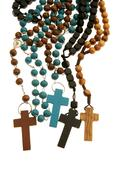 Many different wood rosaries or necklaces united on white Stock Photos