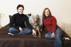 A same sex couple, two women posing with their weimeranar pedigree dog betwee Stock Photos