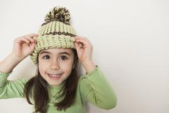 A young child with long brown hair, wearing a knitted hat with a pompom, peer Stock Photos