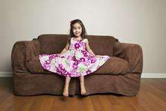 A 3 year old girl with long brown hair in a pink flowered cotton dress with t Stock Photos