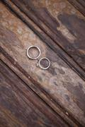Platinum wedding rings . two rings on a worn scrubbed stained wooden surface. Stock Photos