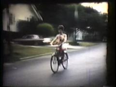 Kids and adults riding bikes down street, mid 1960's Stock Footage