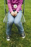 a ten year old girl sitting in chair on lush, green grass, holding a dandelio - stock photo