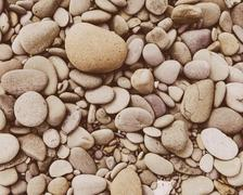 a heap of polished pebbles and small flat stones in olympic national park. - stock photo