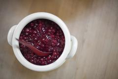 a white pottery bowl, full of fresh cranberries with a matching spoon. a reli - stock photo