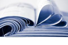 Stack of magazines toned blue isolated Stock Photos