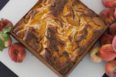 A square baked peach cake on a board with fresh peaches. fruits. organic fres Stock Photos