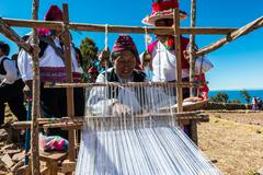 Men weaving in the peruvian andes at puno peru Stock Photos