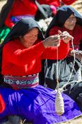 woman weaving in the peruvian andes at puno peru - stock photo