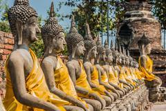 aligned buddha statues wat yai chaimongkol ayutthaya bangkok thailand - stock photo