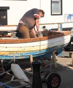 Repairing a small clinker built fishing boat Stock Photos