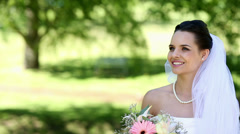 Beautiful bride smiling at camera in the park Stock Footage