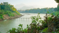 Old bamboo bridge across the river. laos, luang prabang Stock Footage